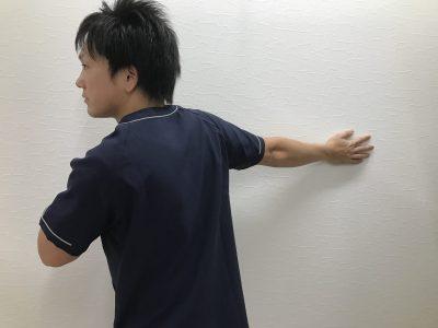 瑞穂市スタッフブログ壁を利用しての胸のストレッチの様子
